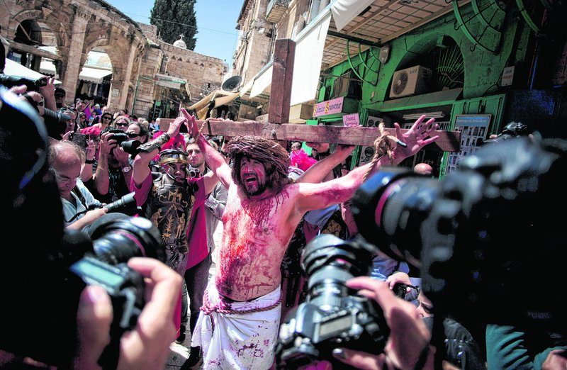 A Christian pilgrim dressed as Jesus Christ is attached to a cross during a reenactment of the crucifixion during a Good Friday procession in Jerusalem on Friday. Israel said it expects some 150,000 visitors during Easter week and the Jewish festival of Passover, which coincide this year.