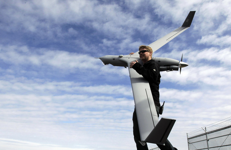 Flight test pilot Alex Gustafson carries an InsituScanEagle unmanned aircraft at Arlington, Ore. Advocates cite numerous examples, from agriculture to mapping, where drones can be valuable as low-cost surveillance tools.