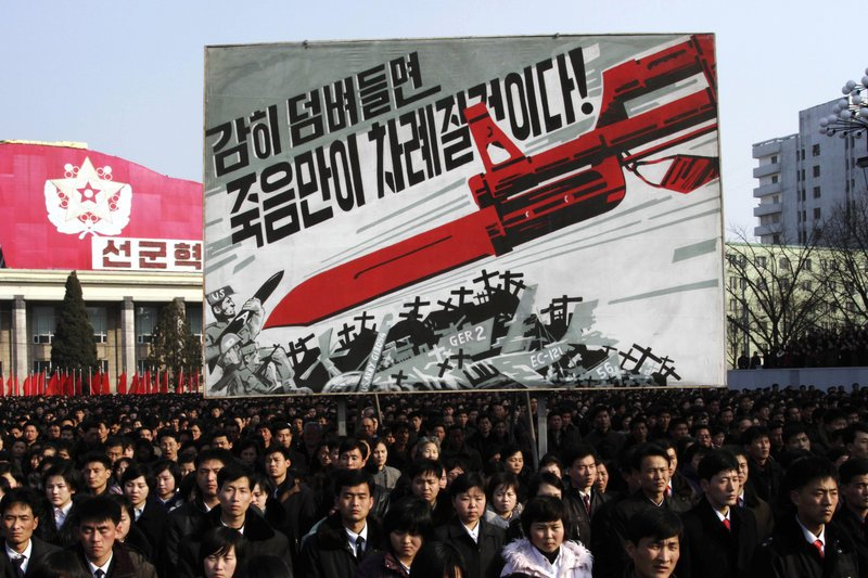 "North Koreans attend a rally earlier this month to support the nation's increasingly belligerent posture toward the West. The sign in the background depicts a large bayonet pointing at U.S. soldiers and says, ""If you dare invade, only death will be waiting for you!"""