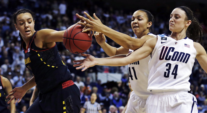 Malina Howard, left, of Maryland reaches for a rebound along with Connecticut's Kiah Stokes, center, and Kelly Faris during UConn's 76-50 victory Saturday in Bridgeport, Conn.