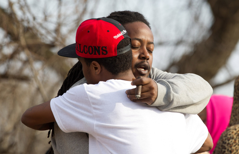 Leaman Joe, left, hugs Michael Parker at the site of the crash that killed their friends in Warren, Ohio, on Sunday.