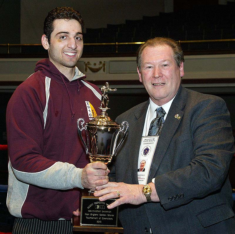 Tamerlan Tsarnaev, left, is shown accepting the trophy for winning the 2010 New England Golden Gloves Championship from Dr. Joseph Downes in Lowell, Mass., on Feb. 17, 2010. Tsarnaev was killed overnight on Friday and the hunt is on for his brother.