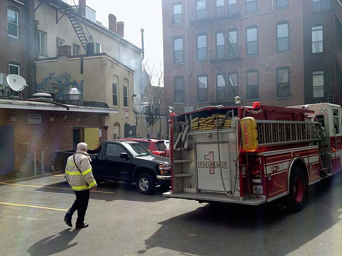 Firefighters investigate a fire in a building at 86 Exchange St. in Portland on Monday.