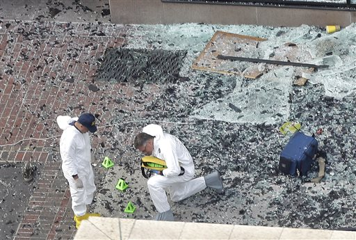 Two men in hazardous materials suits put numbers on the shattered glass and debris as they investigate the scene at the first bombing on Boylston Street near the finish line of the 2013 Boston Marathon, a day after two blasts killed three and injured over 170 people.
