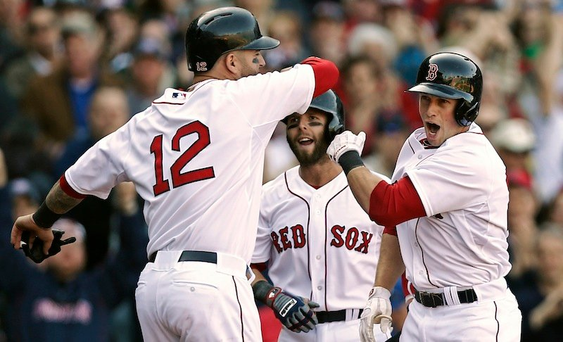 Boston Red Sox's Daniel Nava, right, is greeted by Dustin Pedroia and Mike Napoli (12) after hitting a three-run home run during the seventh inning of a baseball game against the Baltimore Orioles at Fenway Park in Boston, Monday, April 8, 2013. (AP Photo/Winslow Townson)