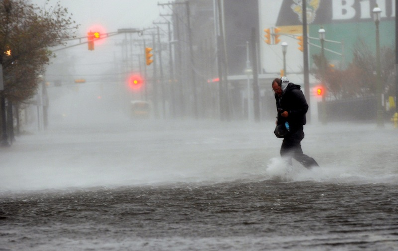 Michael Wirtz, of Wilmington, Del., braves flood waters and high winds that arrive with Hurricane Sandy along North Michigan Avenue in Atlantic City, N.J., Monday Oct. 29, 2012. Hurricane Sandy continued on its path Monday, forcing the shutdown of mass transit, schools and financial markets, sending coastal residents fleeing for higher ground, and threatening a dangerous mix of high winds and soaking rain. (AP Photo/The Press of Atlantic City, Michael Ein)