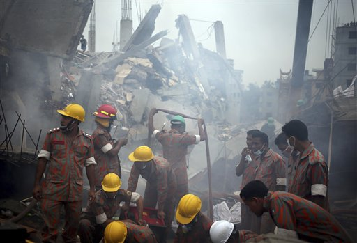 Workers and firefighters prepare to dislodge debris and the fallen ceiling of the garment factory building that collapsed in Savar, Bangladesh. Rescue workers gave up hopes of finding any more survivors in the remains of the building that collapsed five days ago, and began using heavy machinery on Monday to dislodge the rubble and look for bodies.