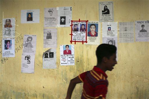 A boy runs past a school turned makeshift morgue with portraits of missing garment factory workers plastered over its walls on Monday.