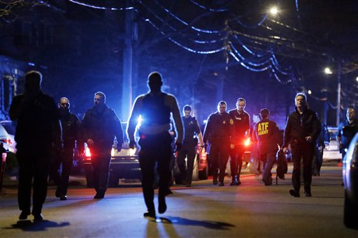 Police converge on a neighborhood where residents heard gunfire and explosions Friday in Watertown, Mass. A tense night of police activity that left a university officer dead on campus just days after the Boston Marathon bombings and amid a hunt for two suspects.