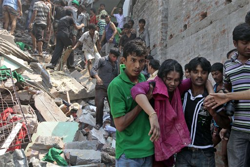 Rescuers assist an injured woman after an eight-story building housing several garment factories collapsed in Savar, near Dhaka, Bangladesh, on Wednesday.