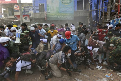 Bangladeshi rescue workers and media fall on top of each other in a stampede aftersomeone shouted that a section of building might collapse in Savar, Bangladesh, on Friday.