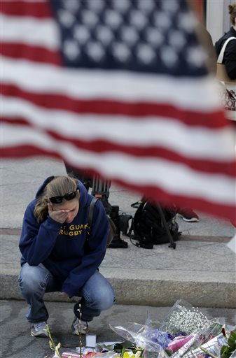 Jillian Blenis, 30, of Boston, reacts while stopping at a makeshift memorial on Wednesday in Boston.