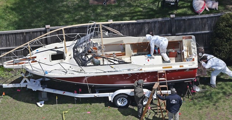 The boat where the bombing suspect was found is inspected by the FBI in a yard on Franklin Street in Watertown. It shows spattered blood on the wheel fenders of a boat trailer along with bullet holes.