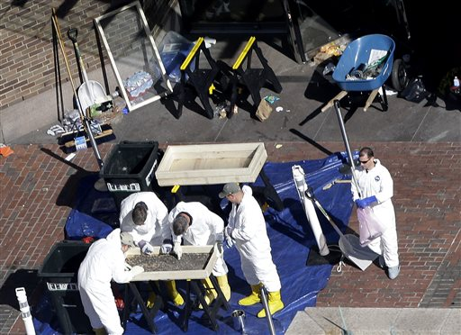 Investigators inspect the area between the two blast sites near the Boston Marathon finish line on Thursday in Boston. Boston remained under a heavy security presence, with scores of National Guard troops gathering among armored Humvees in the Boston Common.