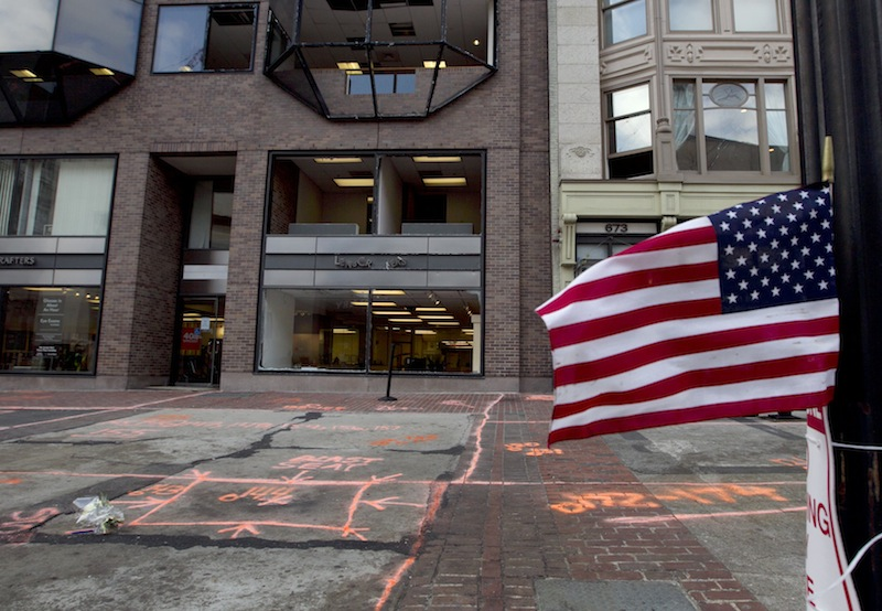 A flag flies at the blast site on Boylston Street between Dartmouth and Exeter Streets near the Boston Marathon finish line Monday, April 22, 2013 in Boston. Federal investigators formally released the finish line bombing crime scene to the city in a brief ceremony at 5 p.m. (AP Photo/Robert F. Bukaty)