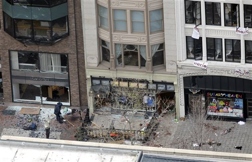 The storefront of Marathon Sports on Boylston Street, near the finish line of the 2013 Boston Marathon, a store owned by former Hall-Dale High School student Colin Peddie, is investigated by a person in a protective suit in the wake of two blasts in Boston on Monday.