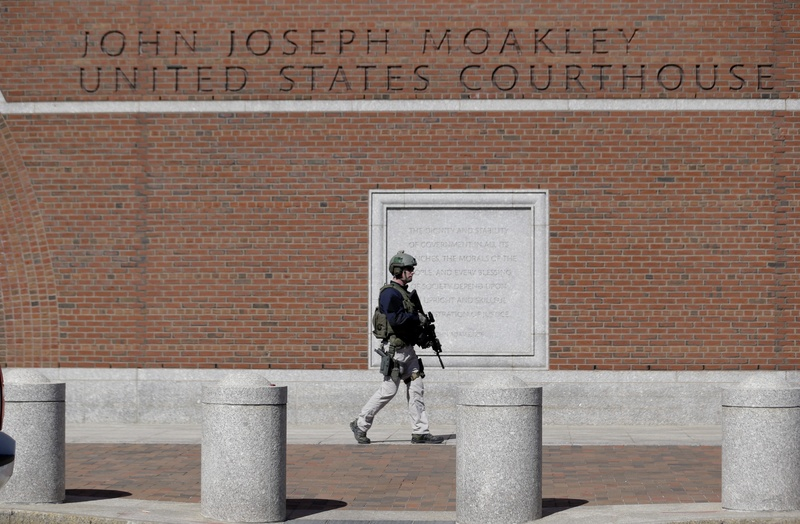 A law enforcement officer wearing tactical gear stands guard outside the John Joseph Moakley Federal Courthouse, which was evacuated Wednesday in Boston.
