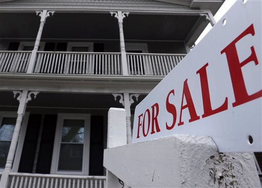 A for sale sign hangs in front of a house in Plymouth, Mass., recently.
