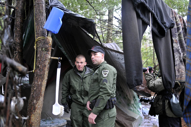 Staff photo by Andy Molloy Game Warden Sgt. Terry Hughes, right and District Warden Dave Ross inspect Christopher Knight's camp Tuesday April 9, 2013 in a remote, wooded section of Rome. Police believe Knight, who went into the woods near Belgrade in 1986, was a hermit who committed hundreds of burglaries to sustain himself.
