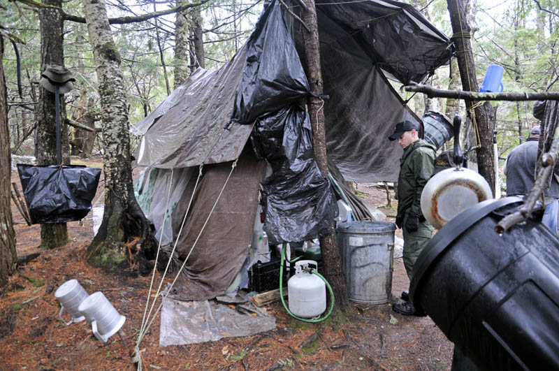 Staff photo by Andy Molloy District Game Warden Aaron Cross inspects Christopher Knight's camp Tuesday April 9, 2013 in a remote, wooded section of Rome. Police believe Knight, who went into the woods near Belgrade in 1986, was a hermit who committed hundreds of burglaries to sustain himself.