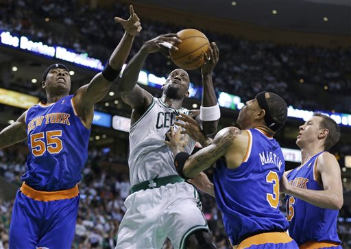 Boston Celtics center Kevin Garnett pulls down an offensive rebound against New York Knicks forward Quentin Richardson (55), forward Kenyon Martin (3) and forward Steve Novak (16) during the first half in Sunday's Game 4 of a first-round NBA basketball playoff series in Boston. TD Garden