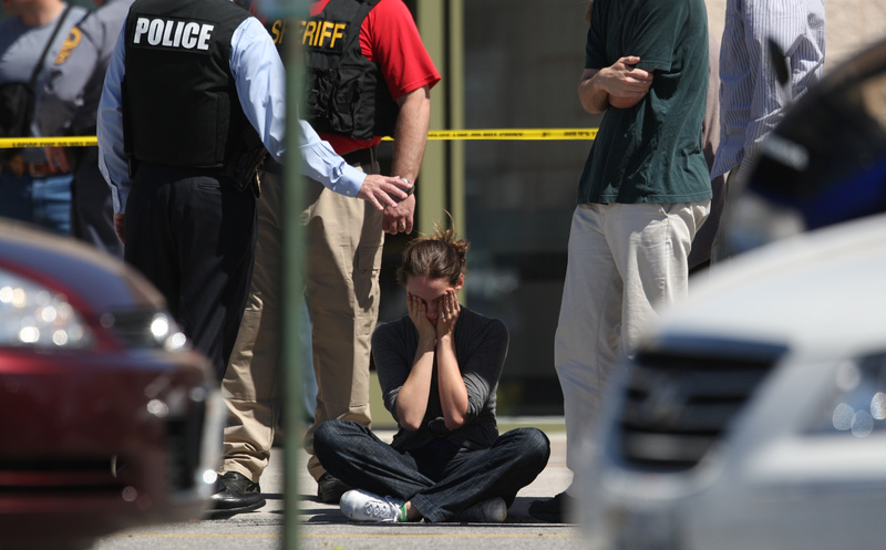 Clara Keller, of Blacksburg, Va., holds her head as she sits on the sidewalk near law enforcement officers outside the New River Valley Mall in Christiansburg, Va., on Friday. VIRGINIA