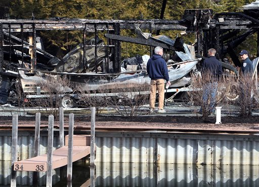 Investigators inspect what's left of boats on Monday after a fire damaged about 30 boats at the Riveredge Marina in Ashland, N.H.