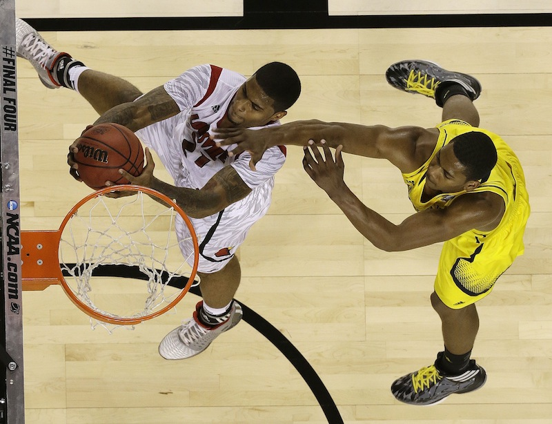 Louisville forward Chane Behanan (21) shoots over Michigan forward Glenn Robinson III (1) during the second half of the NCAA Final Four tournament college basketball championship game Monday, April 8, 2013, in Atlanta. (AP Photo/Charlie Neibergall)