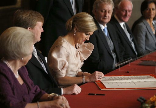 Queen Maxima, right, signs the Act of Abdication after it was signed by King Willem-Alexander, centre, and Queen Beatrix, left, in the Mozeszaal or Mozes hall of the Royal Palace in Amsterdam on Tuesday.
