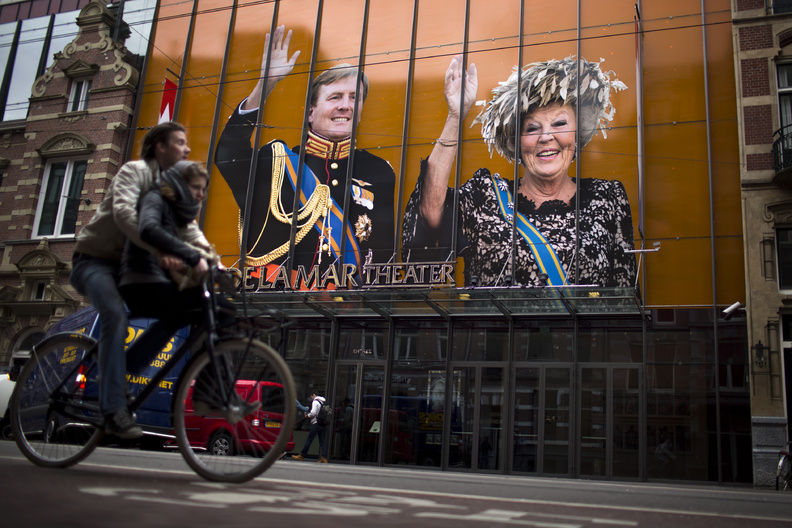 A cyclist passes by an image of Dutch Queen Beatrix and her son Crown Prince Willem-Alexander on the exterior of a theater in downtown Amsterdam, Netherlands, on Monday. Queen Beatrix will relinquish the crown on Tuesday, after 33 years of reign, leaving the monarchy to her son.