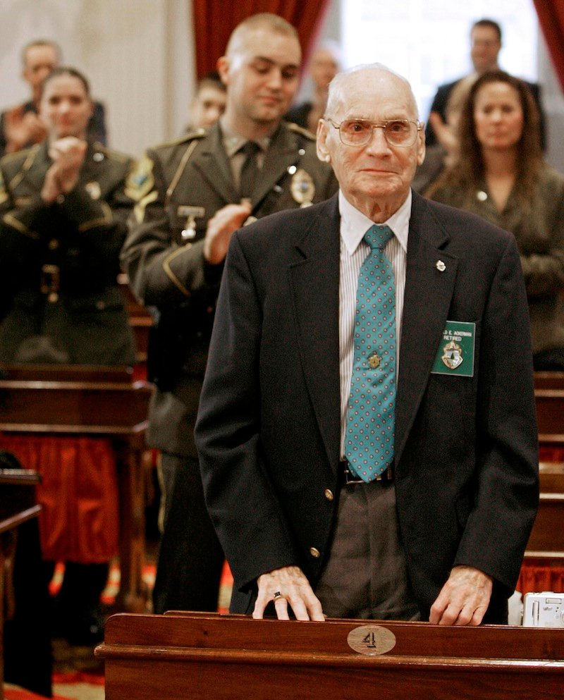 """In this Dec. 15, 2006 file photo, former Vermont State Police Lt. Harold """"Ace"""" Ackerman, 86, of St. Johnsbury, Vt. stands to be recognized during an awards ceremony at the Statehouse in Montpelier, Vt. The last surviving member of the original Vermont State Police has died. Ackerman died Monday at his home in St. Johnsbury. He was 92. The state police was formed after a 1946 search for a missing Bennington College student proved too complex for local authorities. Ackerman was one of the original troopers when the Vermont State Police was formed from the Department of Motor Vehicles' highway patrol. (AP Photo/Toby Talbot)"""