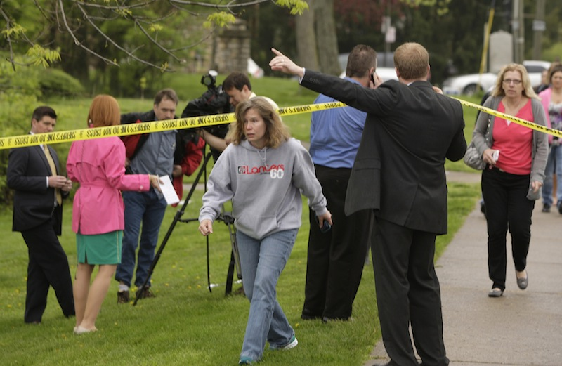 Parents and other family members cross under a police line to check on their children, Monday, April 29, 2013, at LaSalle High School in Cincinnati, where a high school student pulled out a gun and shot himself in a classroom on Monday. The Hamilton County sheriff's office says the youth was taken to a hospital with a self-inflicted wound. They say there apparently was no threat to other students at the private school. (AP Photo/Cincinnati Enquirer, Glenn Hartong)