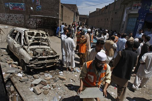 People gather at the site of an explosion outside an election office of a candidate in Peshawar, Pakistan, Sunday.