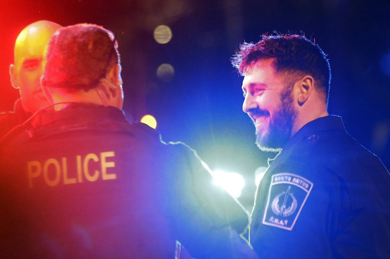 Police officers smile to fellow officers as they leave the scene after the arrest of a suspect of the Boston Marathon bombings in Watertown, Mass., Friday, April 19, 2013. A 19-year-old college student wanted in the Boston Marathon bombings was taken into custody Friday evening after a manhunt that left the city virtually paralyzed and his older brother and accomplice dead. (AP Photo/Matt Rourke)