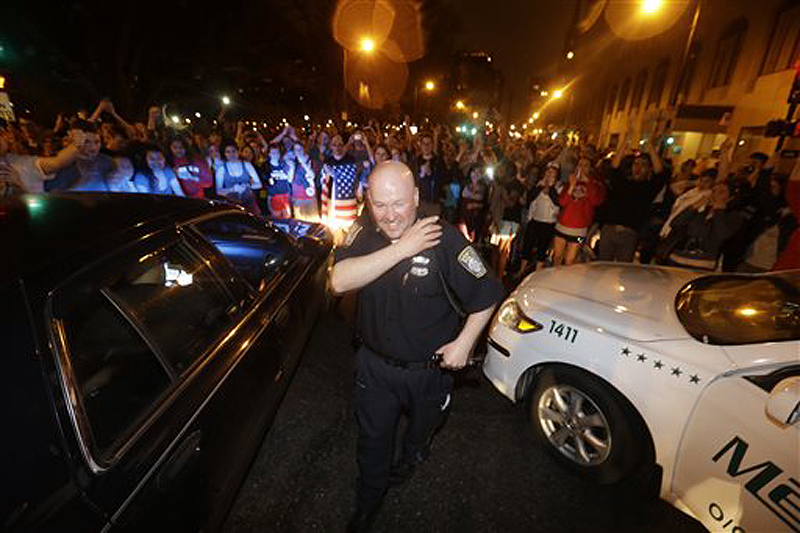 A police officer reacts to news of the arrest of one of the Boston Marathon bombing suspects on Friday in Boston. Dzhokhar Tsarnaev was captured in Watertown, Mass., after a manhunt that left the city virtually paralyzed.