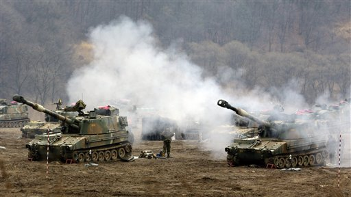 South Korean Marines' K-55 self-propelled howitzers are covered by smoke during a military exercise in the border city between two Koreas, Paju, north of Seoul, South Korea on Tuesday, as North Korea vows to restart a nuclear reactor that can make one bomb's worth of plutonium a year.