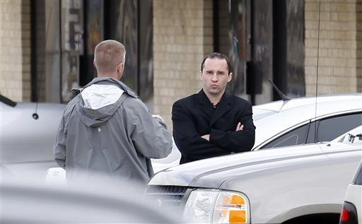 Everett Dutschke, right, confers with a federal agent on Wednesday near the site of a martial arts studio he once operated in Tupelo, Miss. The property was being searched in connection with the investigation into poisoned letters mailed to President Barack Obama and others. Dutschke has not been arrested or charged.