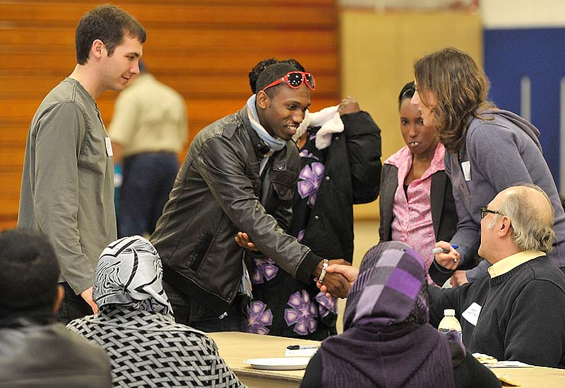 Josh Ntimugura from the congo shakes the hand of John Kavanaugh, father to Laragh Kavanaugh, right, a mentoring volunteer to Josh's sister, Jeanette, middle, as the large group of attendees met each other and found new friends in the community during New Mainers Day Saturday at the Sullivan Recreation and Fitness Complex on the USM Portland Campus.