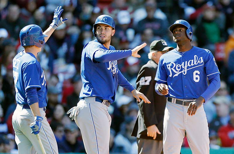 Kansas City's Chris Getz, left, celebrates after Eric Hosmer, center, and Lorenzo Cain score on a single by Salvador Perez in the fourth inning Sunday against the Red Sox at Fenway Park in the first game of a doubleheader.