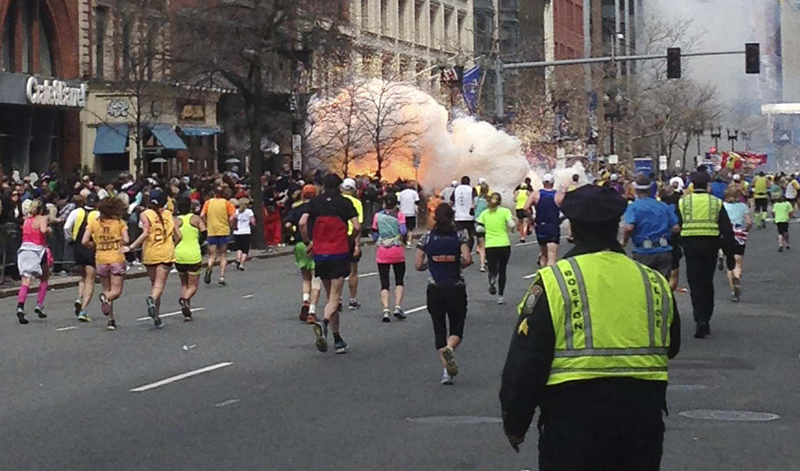 Runners continue to run towards the finish line of the Boston Marathon as an explosion erupts near the finish line of the race in this photo exclusively licensed to Reuters by photographer Dan Lampariello after he took the photo in Boston, Massachusetts, April 15, 2013. Two simultaneous explosions ripped through the crowd at the finish line of the Boston Marathon on Monday, killing at least two people and injuring dozens on a day when tens of thousands of people pack the streets to watch the world famous race. REUTERS EXCLUSIVE REUTERS/Dan Lampariello (UNITED STATES - Tags: CRIME LAW SPORT ATHLETICS TPX IMAGES OF THE DAY ) MANDATORY CREDIT - RTXYN2C :rel:d:bm:GM1E94G0KIH01
