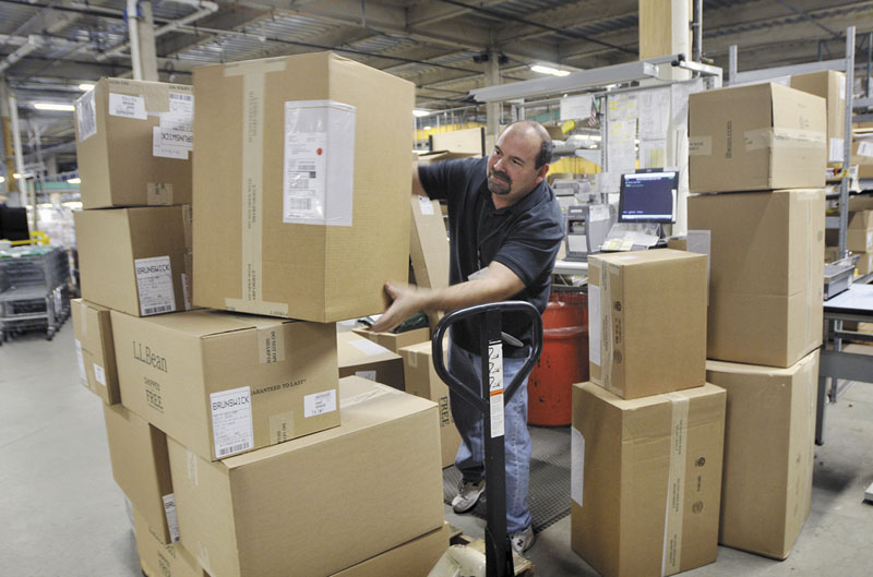 Joe Perron prepares packages to be shipped at the L.L. Bean warehouse in Freeport. States could force Internet retailers to collect sales taxes under a bill that passed a test vote in the Senate. Bean and other retailers hope for more time to comply.