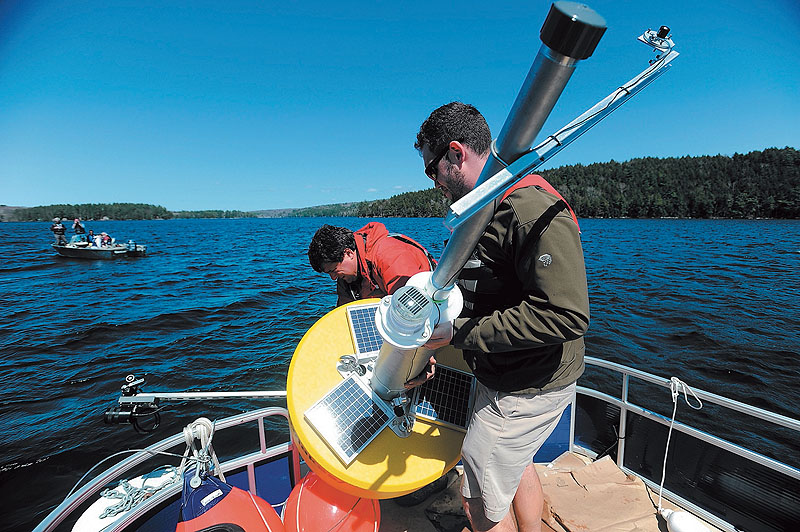 Colby College chemistry professor Whitney King, at rear, and Colby College senior Matt LaPine, 22, install a research buoy named Goldie in Great Pond in Belgrade.