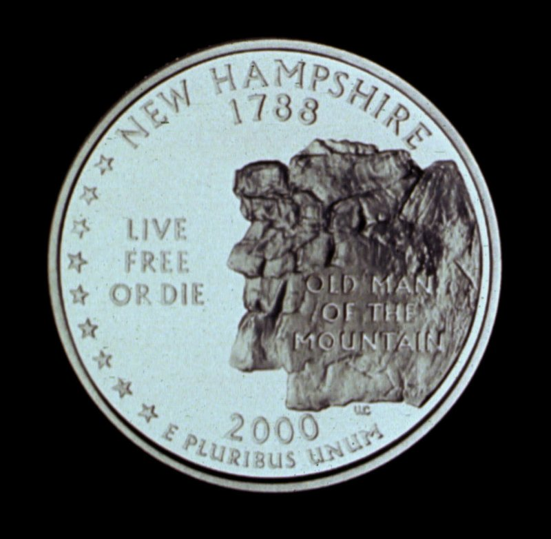 The New Hampshire quarter shows a representation of the Old Man of the Mountain.