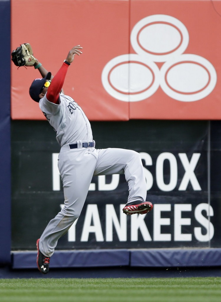 Jackie Bradley Jr. makes an acrobatic catch on Robinson Cano's deep drive to left field in the third inning at Yankee Stadium.