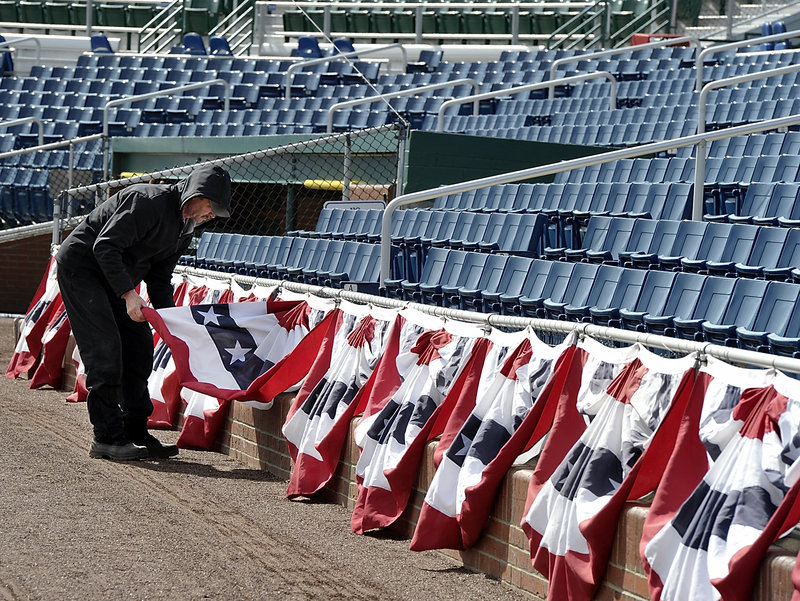Rick Anderson, the head groundskeeper at Hadlock Field, adjusts bunting Tuesday as the Portland Sea Dogs prepare to open their season at 6 p.m. Thursday against the Trenton Thunder.