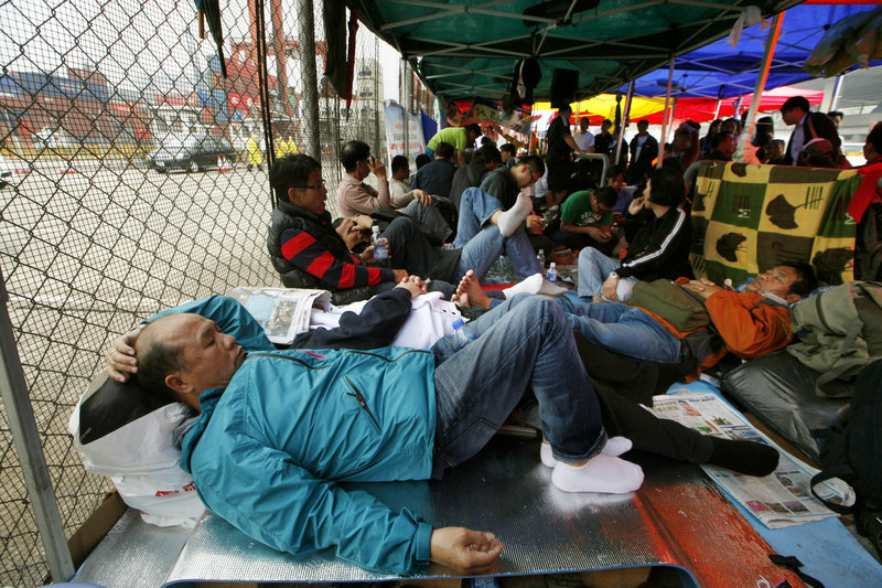 Several hundred dock workers and their supporters camp out Wednesday on the road in front of a container terminal on the seventh day of their strike in Hong Kong.