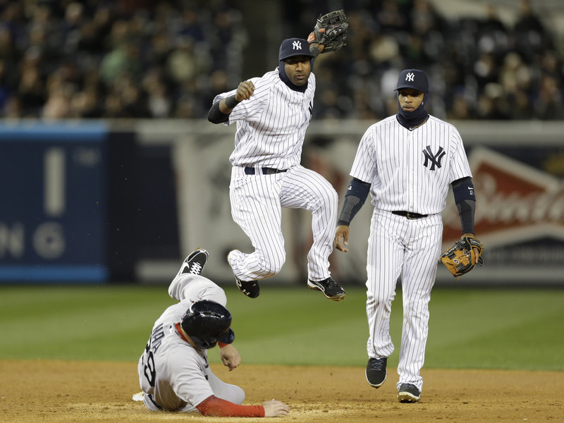 Eduardo Nunez leaps after forcing out Boston's Daniel Nava with Robinson Cano watching in Wednesday night's game at New York. The Red Sox won 7-4.