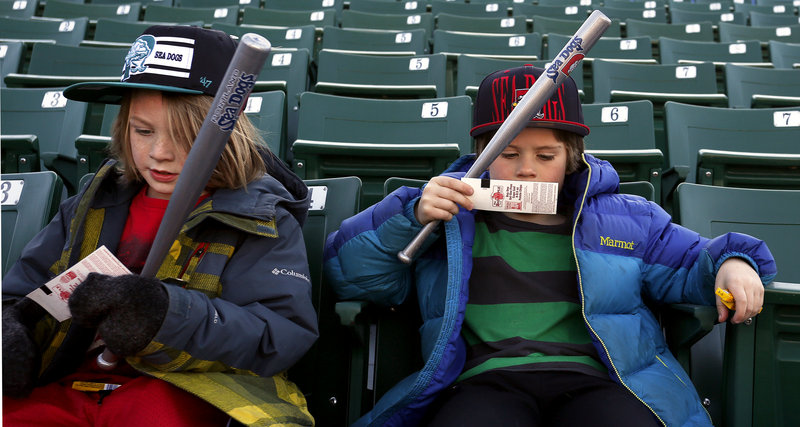 Otis and Eli Evans of Portland check their tickets as they settle in for the Sea Dogs season opener Thursday.