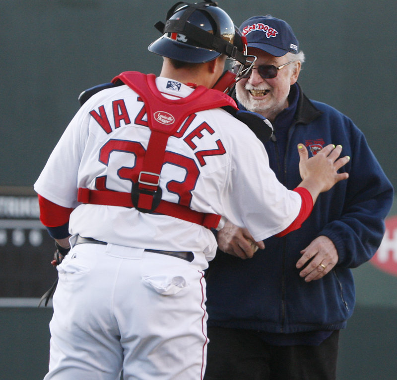 Catcher Christian Vazquez congratulates former Hadlock Field announcer Dean Rogers after Rogers' ceremonial first pitch. The Dogs got their season off to a slow start, losing 13-5.