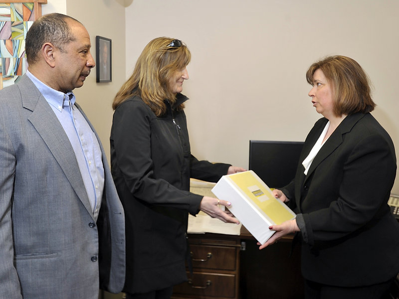 Wayne and Judi Richardson of South Portland give Crystal Canney, communications director for Sen. Angus King, petitions with more than 6,000 signatures in support of federal gun controls at King's Portland office on Friday. The Richardsons' daughter Darien died in 2010 after being shot by an intruder in her apartment.